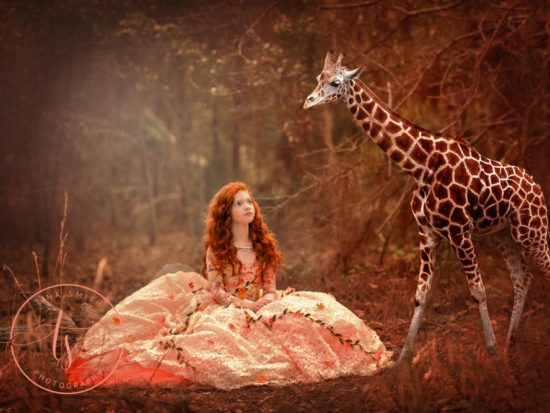 Fantasy portrait of a child in a ball gown next to giraffe