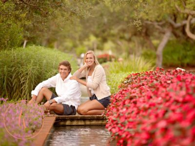 engaged couple man and woman posing among flowers and small pond