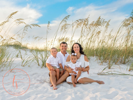 family sitting on beach in destin for photography