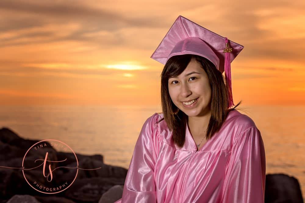 destin florida photographer graduating girl wearing pink cap and gown