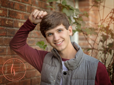 young male high school senior leaning against brick wall wearing vest