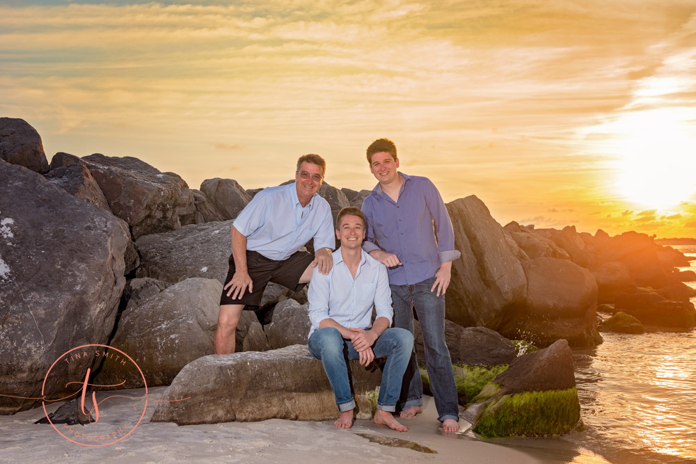 family sitting on rocks at destin jetties at sunset