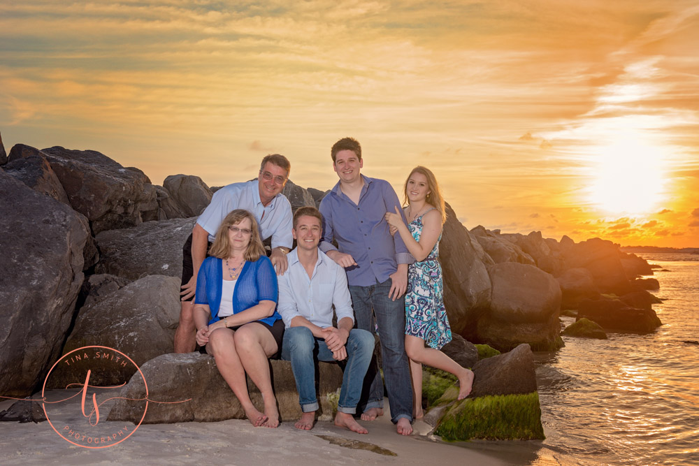 family posing on beach in destin at sunset
