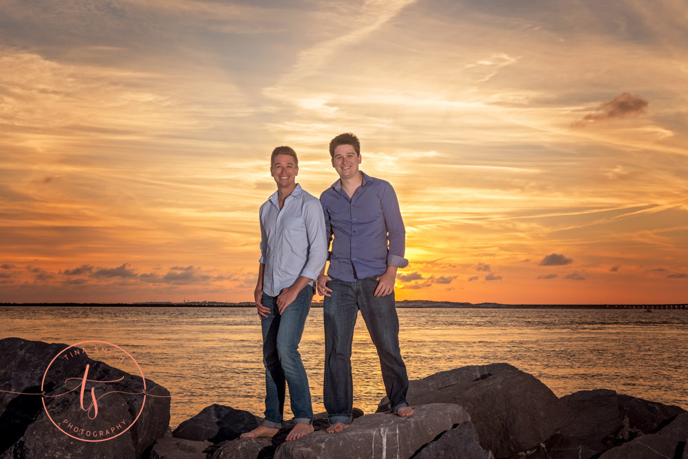 brothers posing on jetty in destin at sunset
