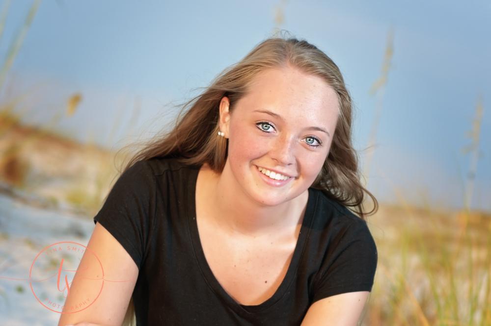 senior girl in black shirt posing on beach in destin