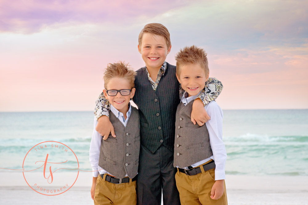 three brothers hugging on the beach at sunrise