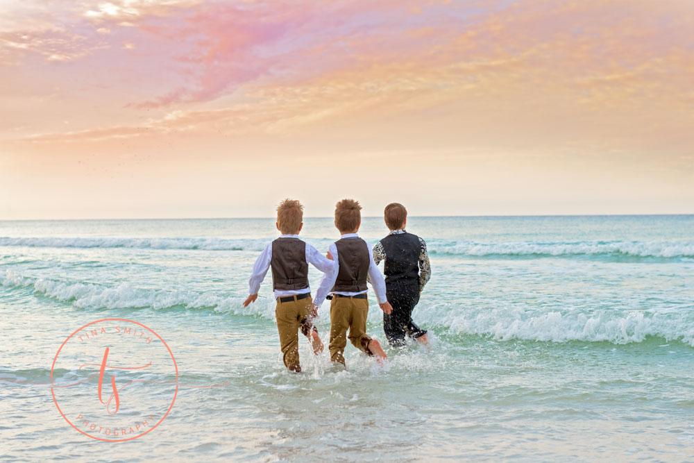 brothers splashing in water on destin beach