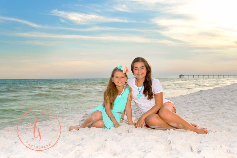 sisters sitting on destin beach posing for photographer