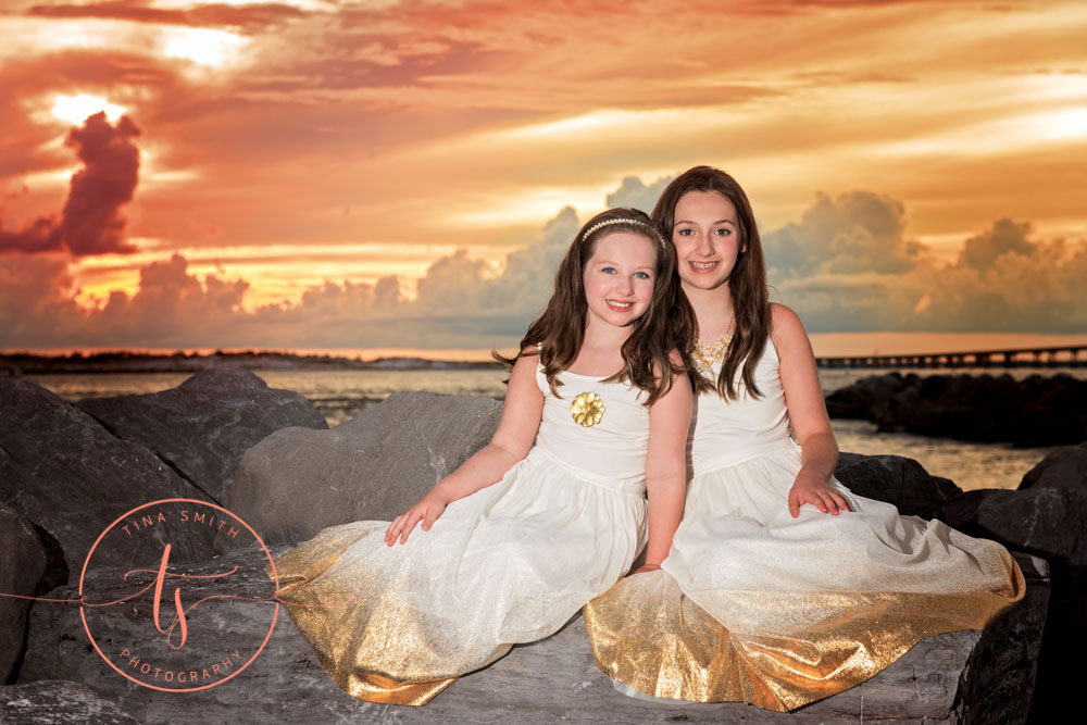 sisters in gold dresses sitting on jetty in destin at sunset