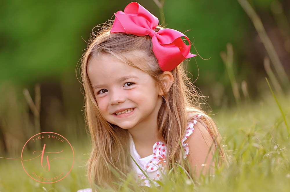 girl in white dress and big pink bow laying in green grass smiling for photographer