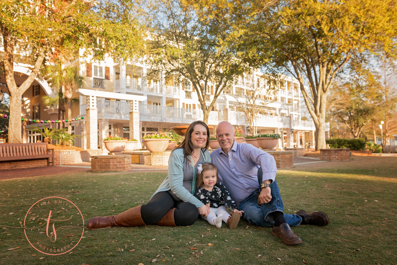 family sitting on lawn baytowne wharf smiling for photographer