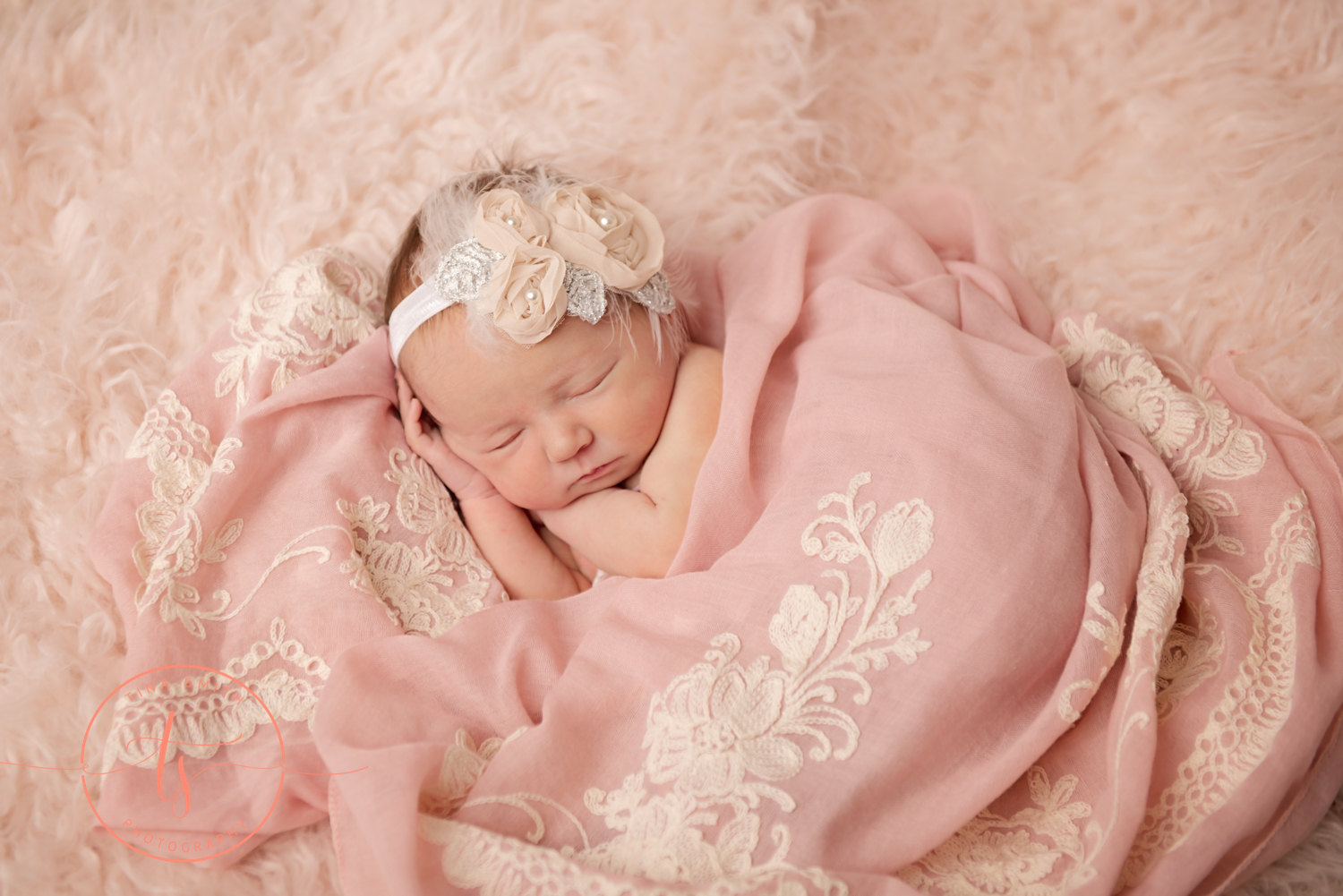 newborn baby on beige fur with pink flowered wrap posed for pictures