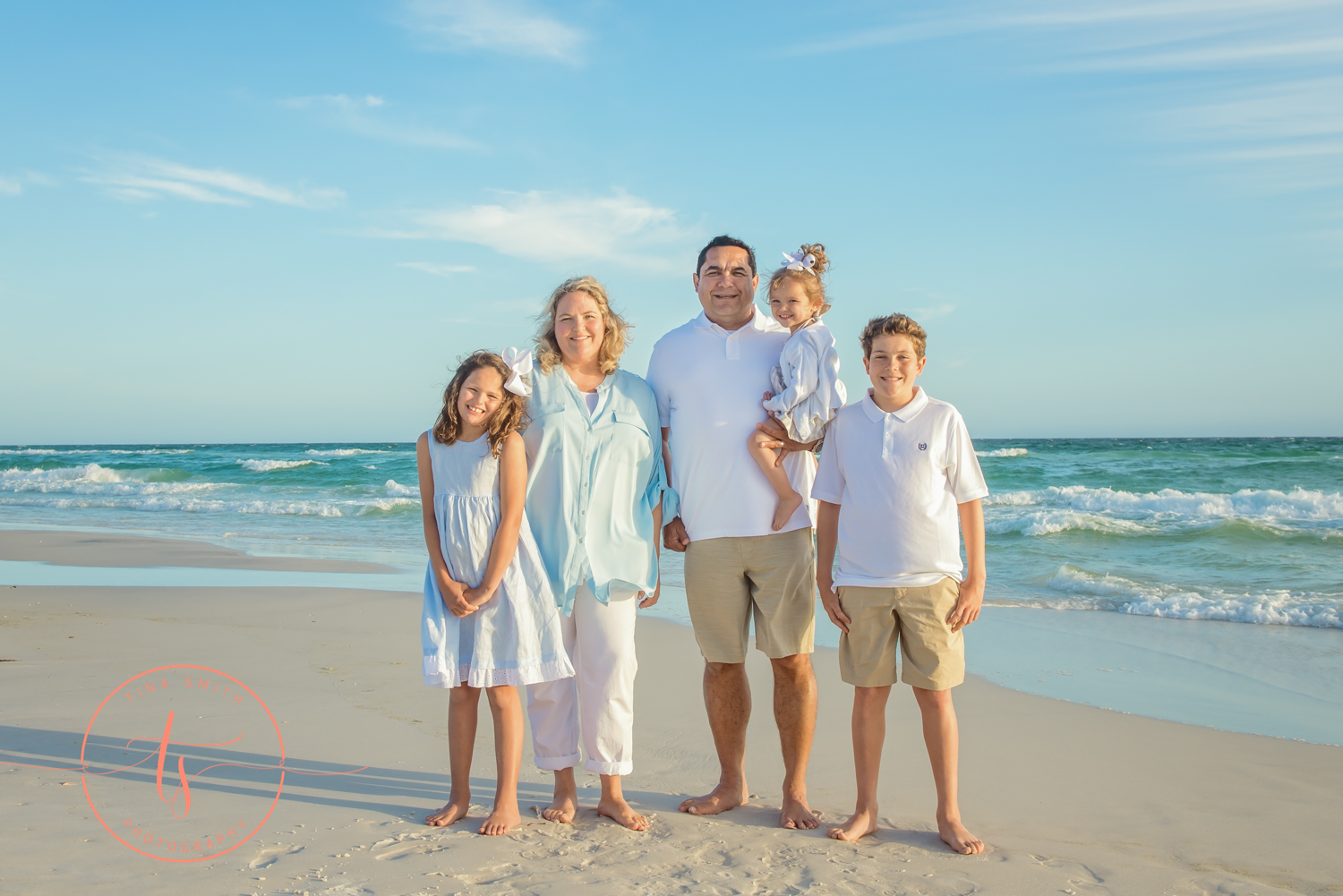 family posing on watersound beach smiling for photographer