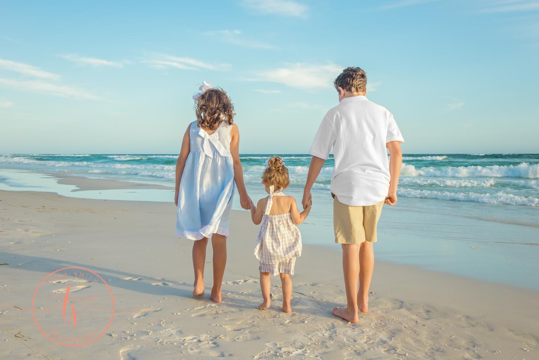 children walking down watersound beach holding hands