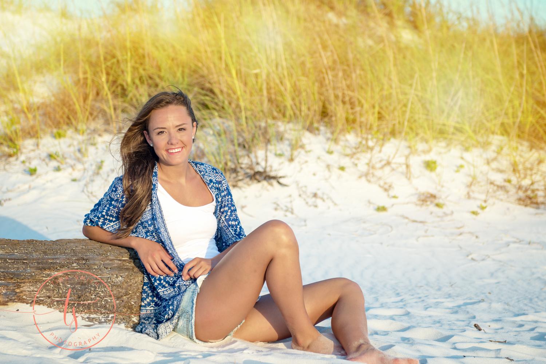 girl leaning on drift wood on beach in destin for senior portraits