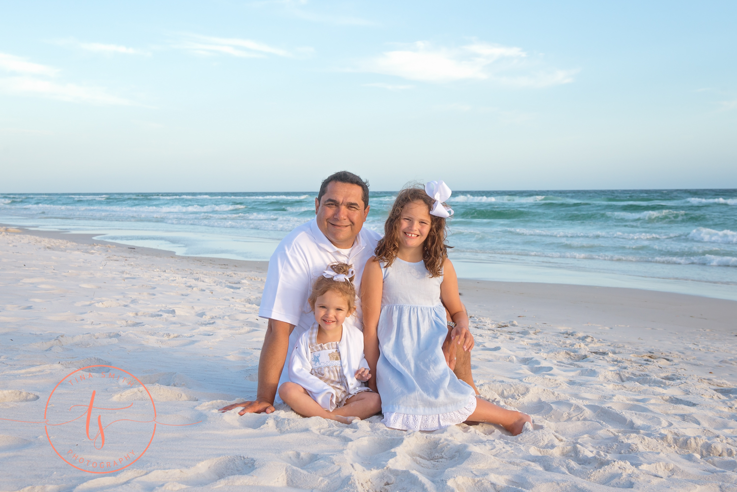 dad and daughters sitting on watersound beach smiling for photographer