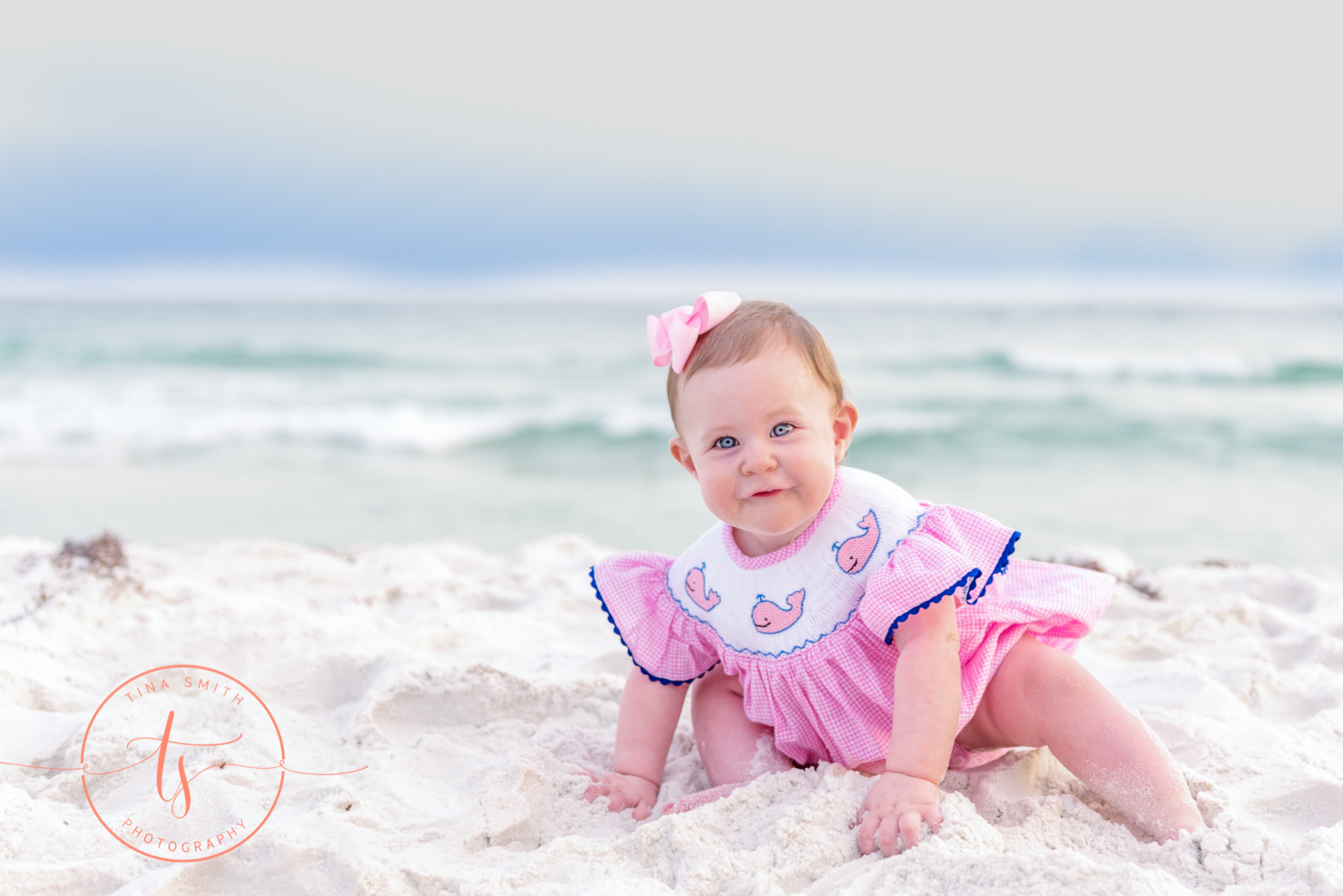 baby girl crawling on beach in dests dressed in pink dress