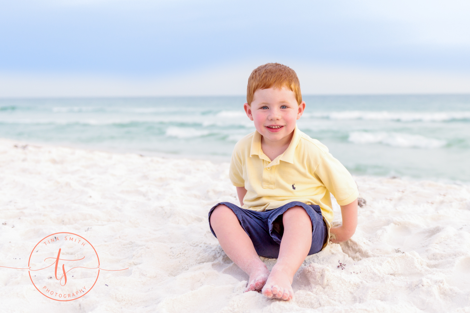 red headed little boy sitting on the beach in destin playing in the sand