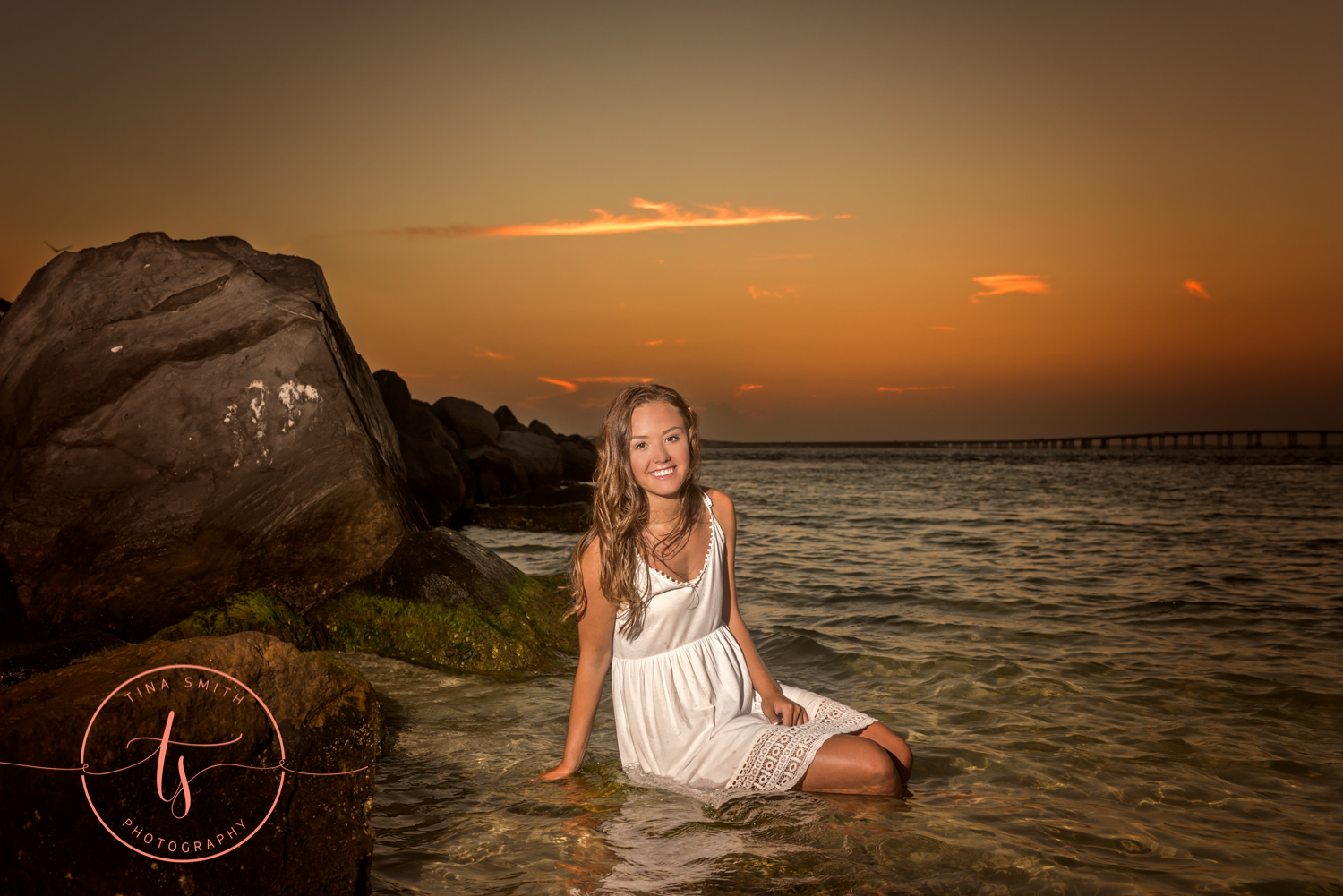 girl in white dress sitting in water at beach in destin