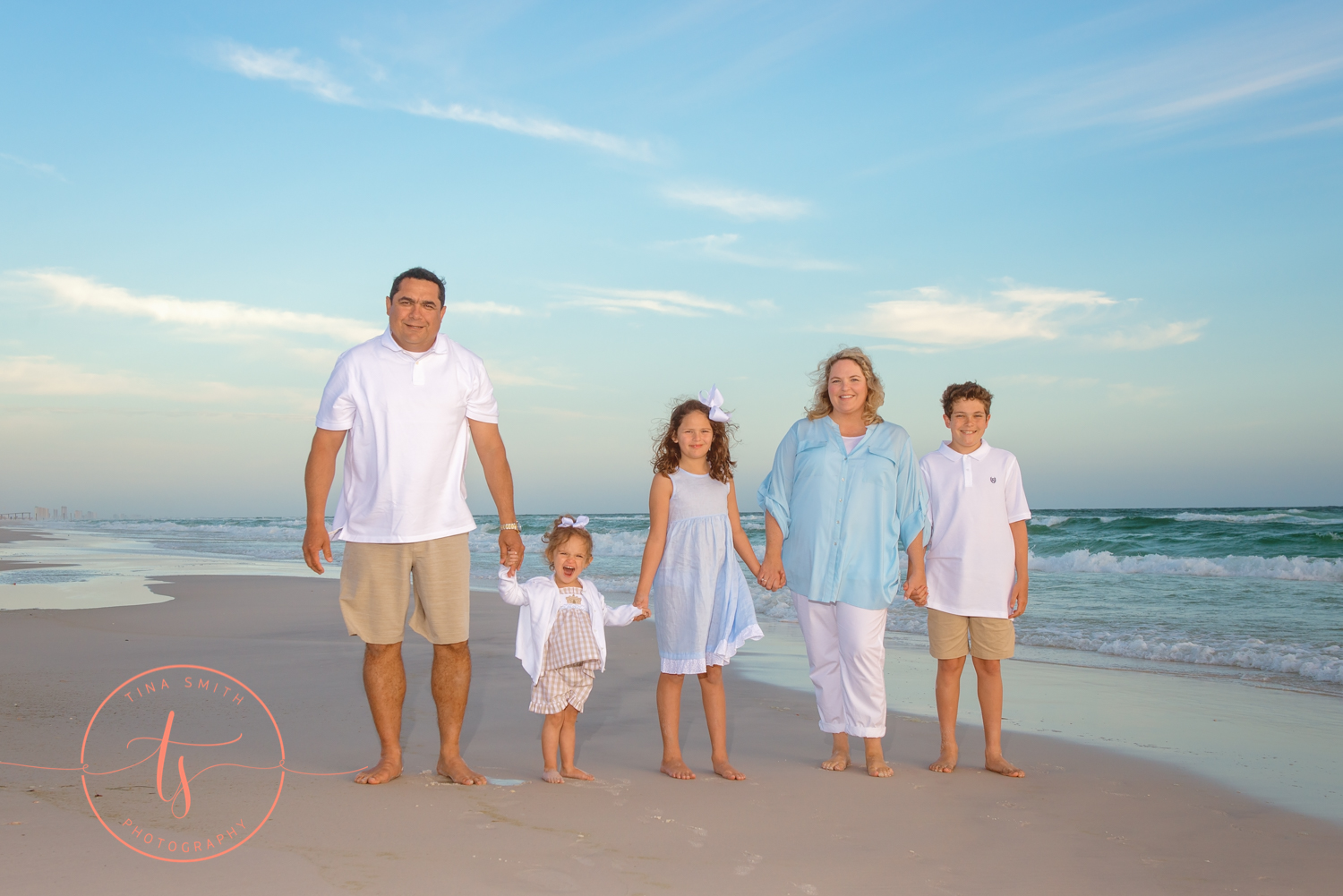 family walking in the waters edge on watersound beach holding hands