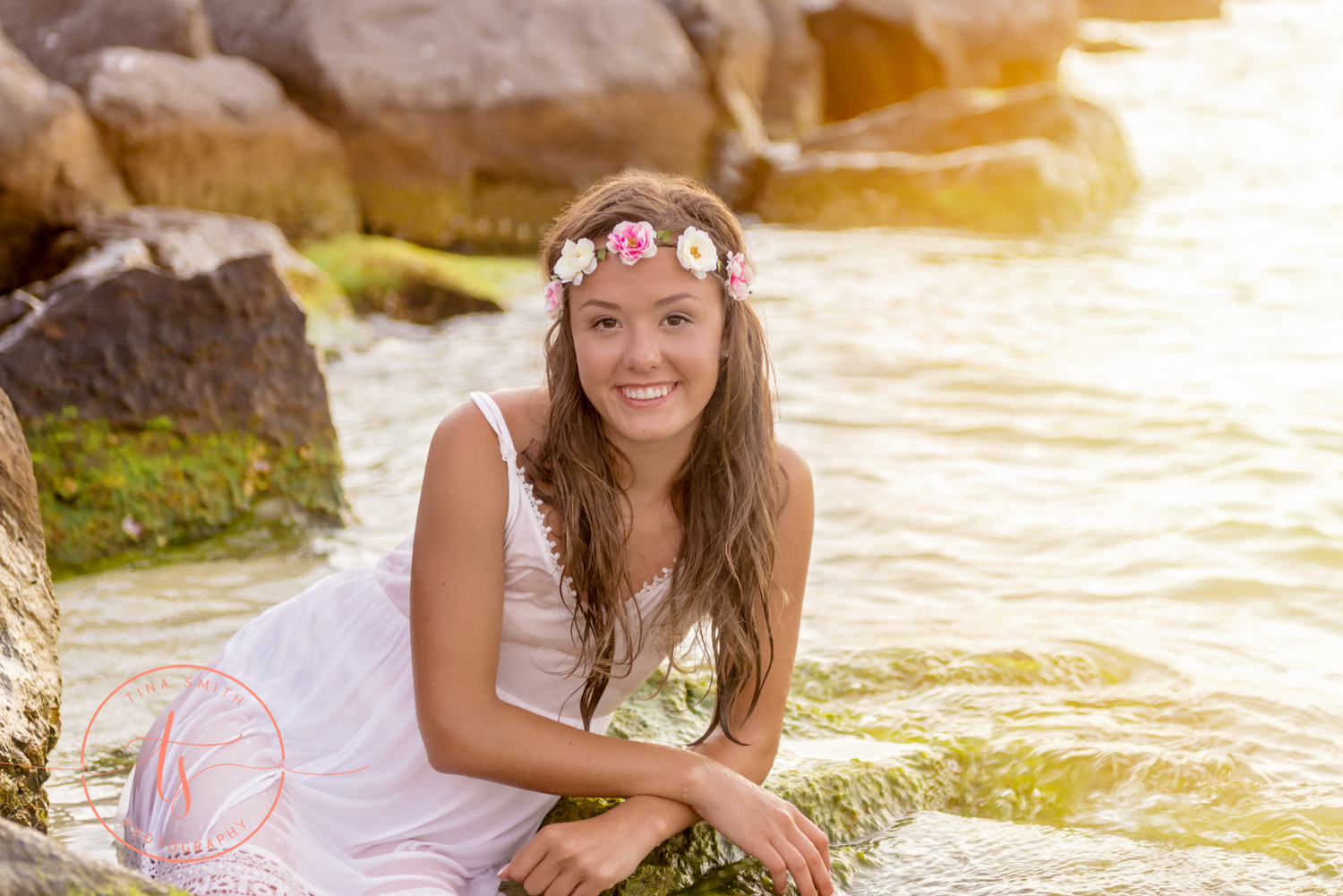 girl in white dress and flower headband lying in water at the beach in destin