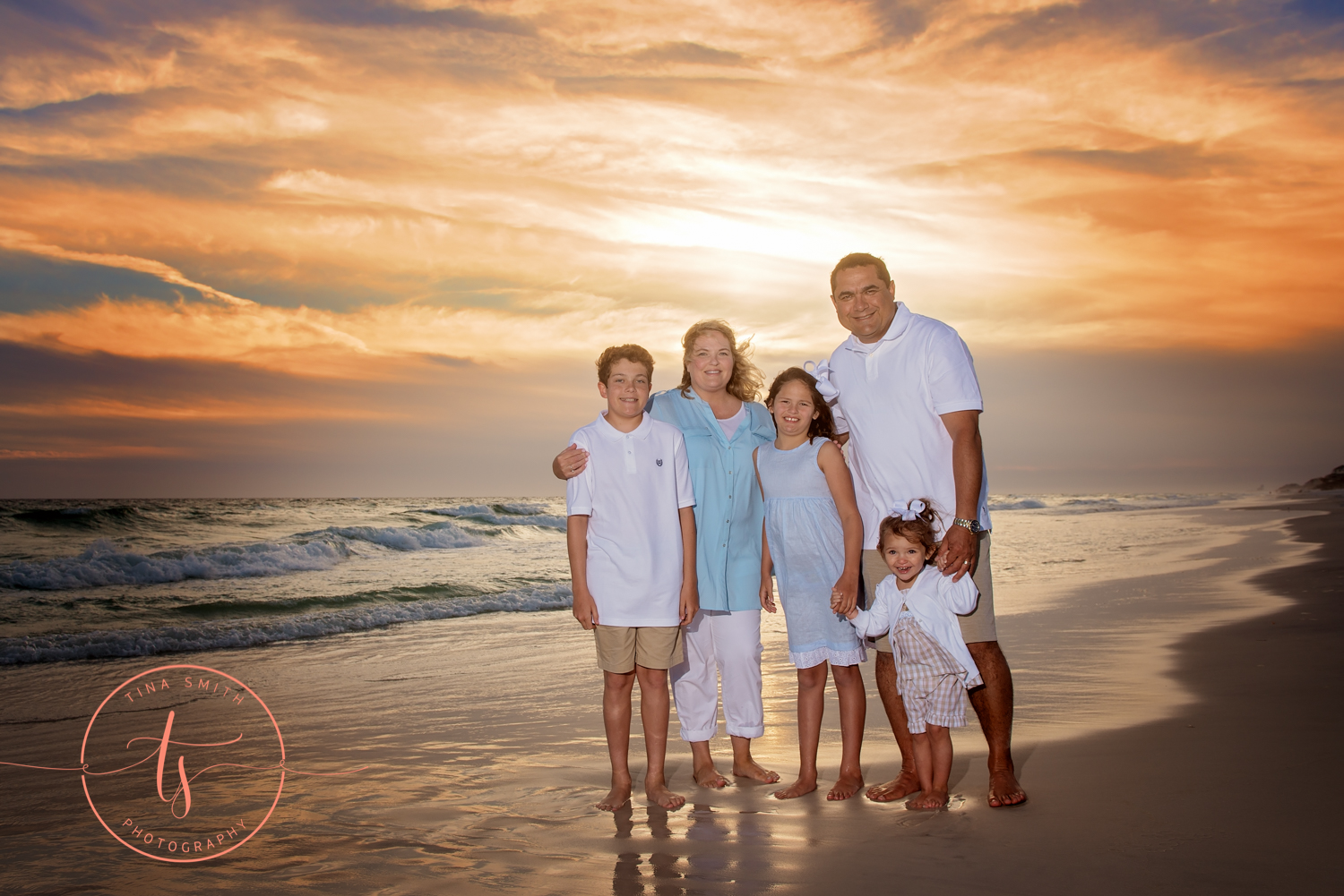 family on watersound beach posing at sunset for photographer