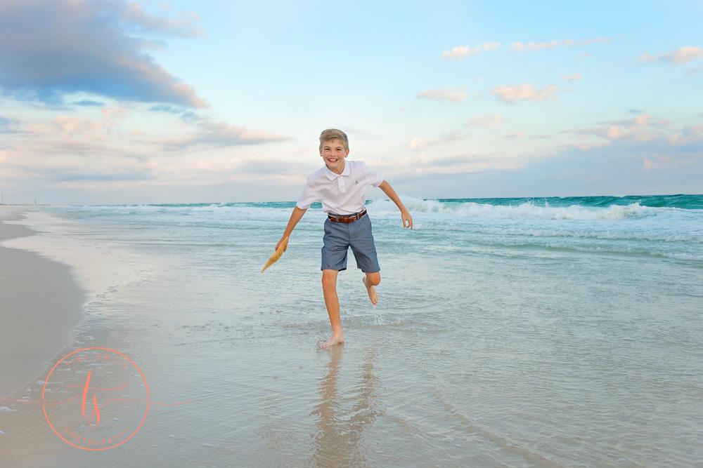 boy splashing on beach in destin