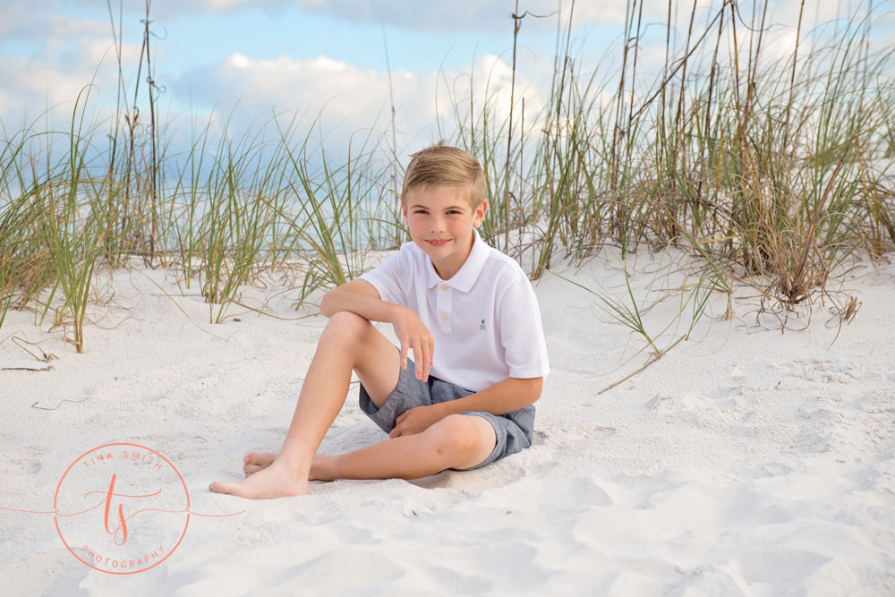 boy sitting in sand in dunes and sea oats