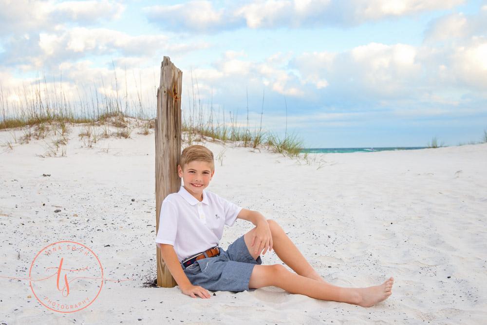 boy leaning against beach pole in destin