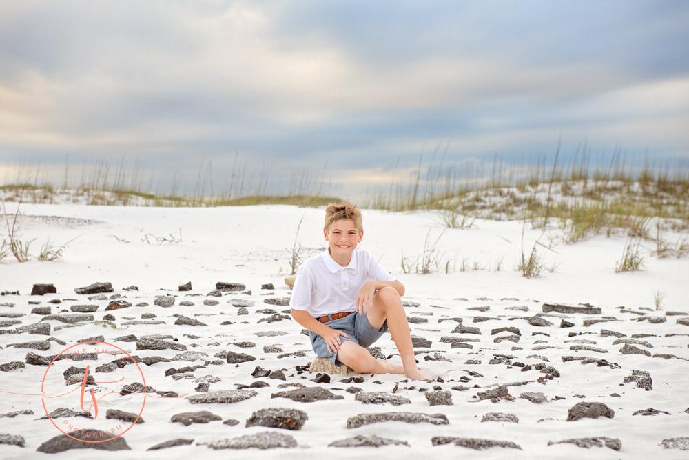 boy sitting in ring of rocks on beach