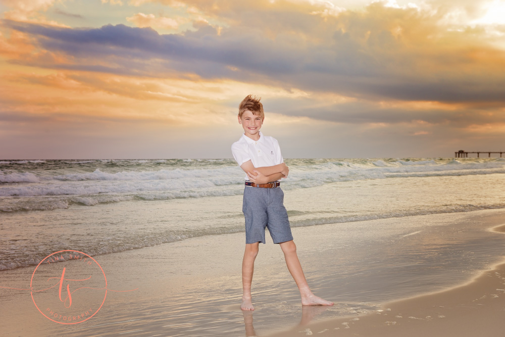boy standing on beach at sunset