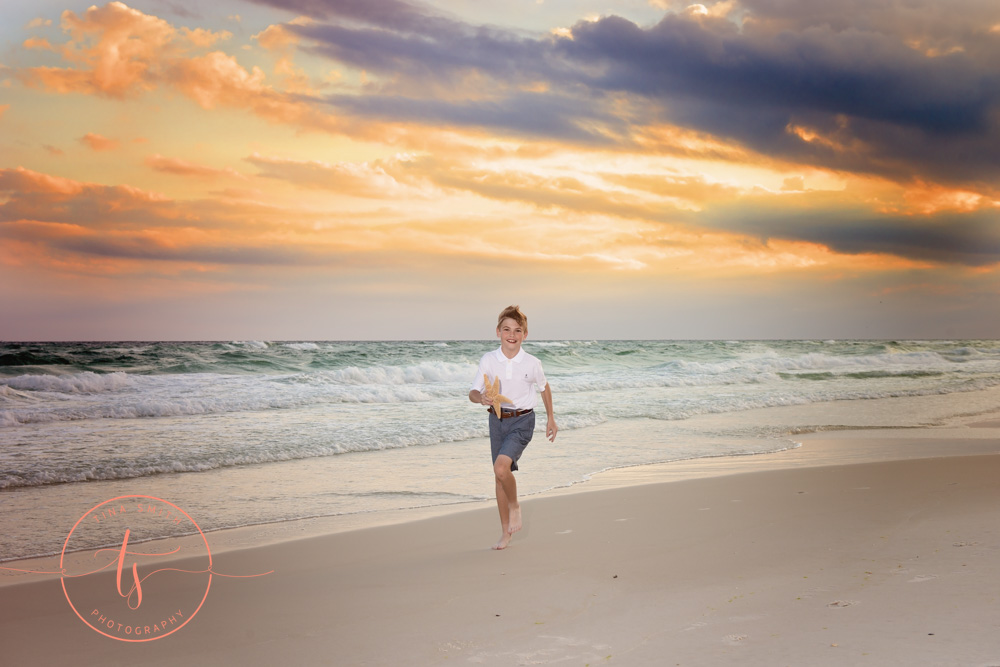 boy waling down beach at sunset
