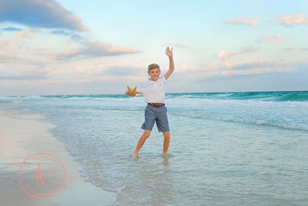 boy splashing in water on beach