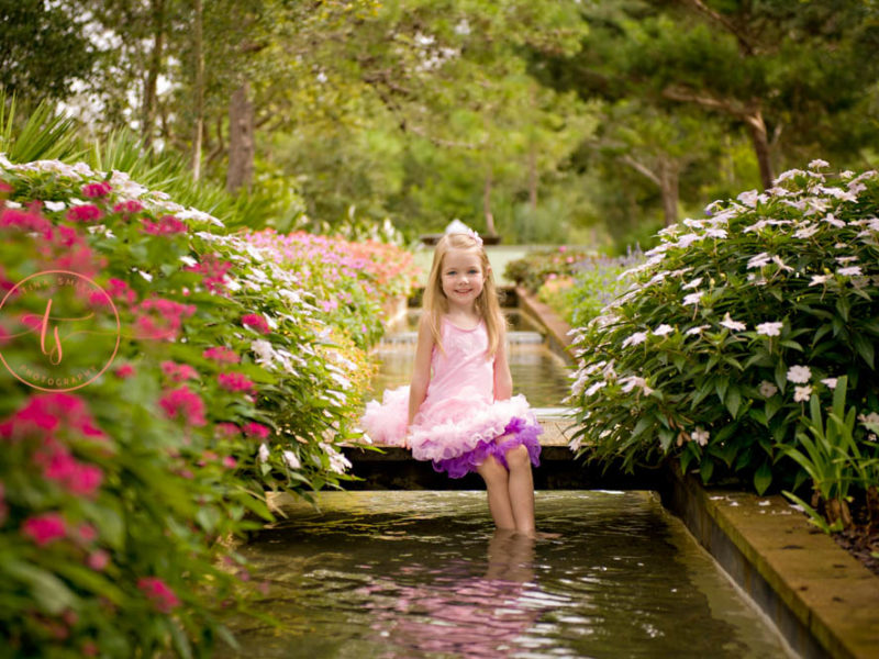 female child sitting by a fountain at a park in baytowne wharf