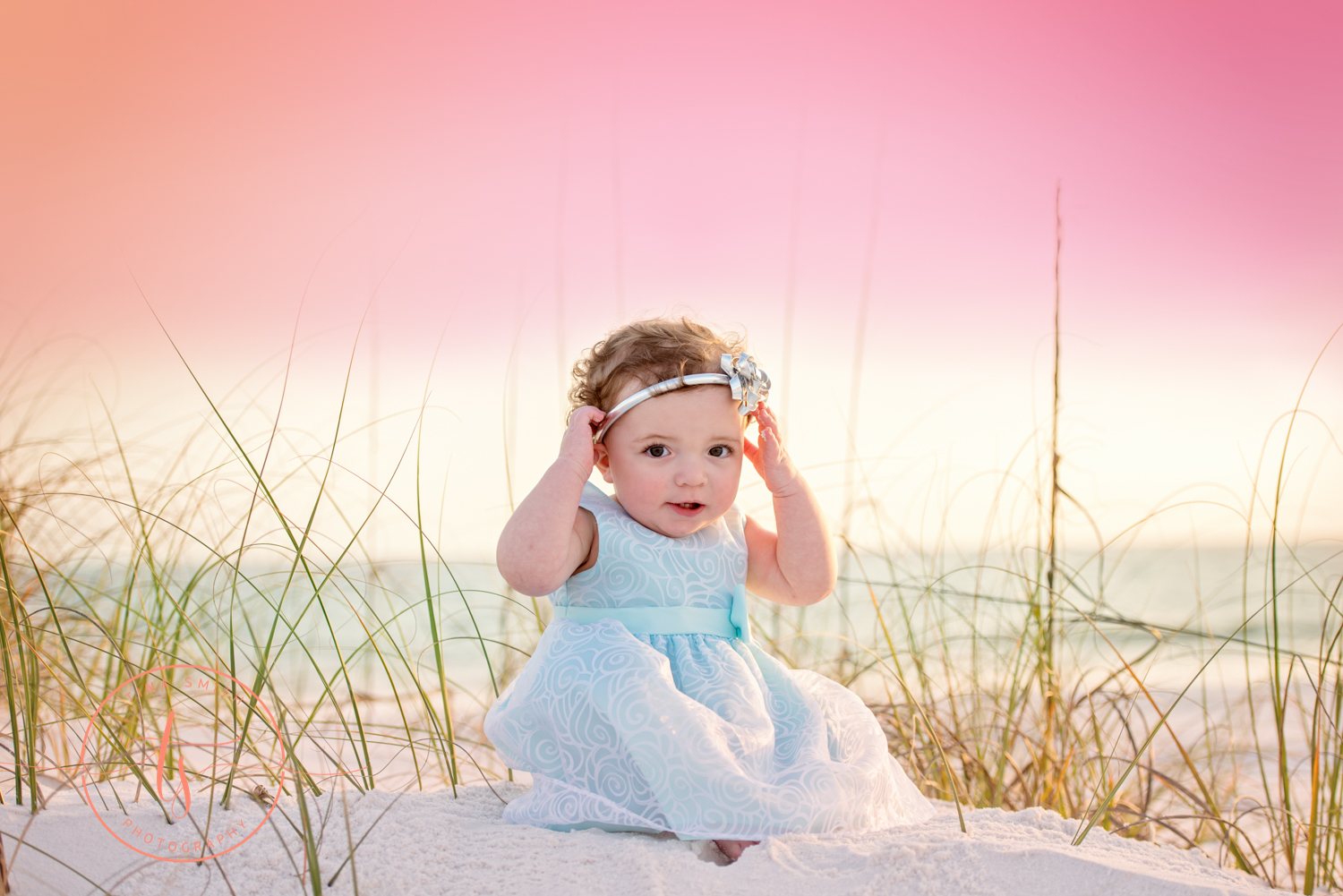 baby girl in lavender dress sitting on beach in destin