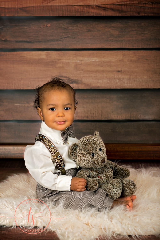 boy holding bear sitting on rug smiling for photographer