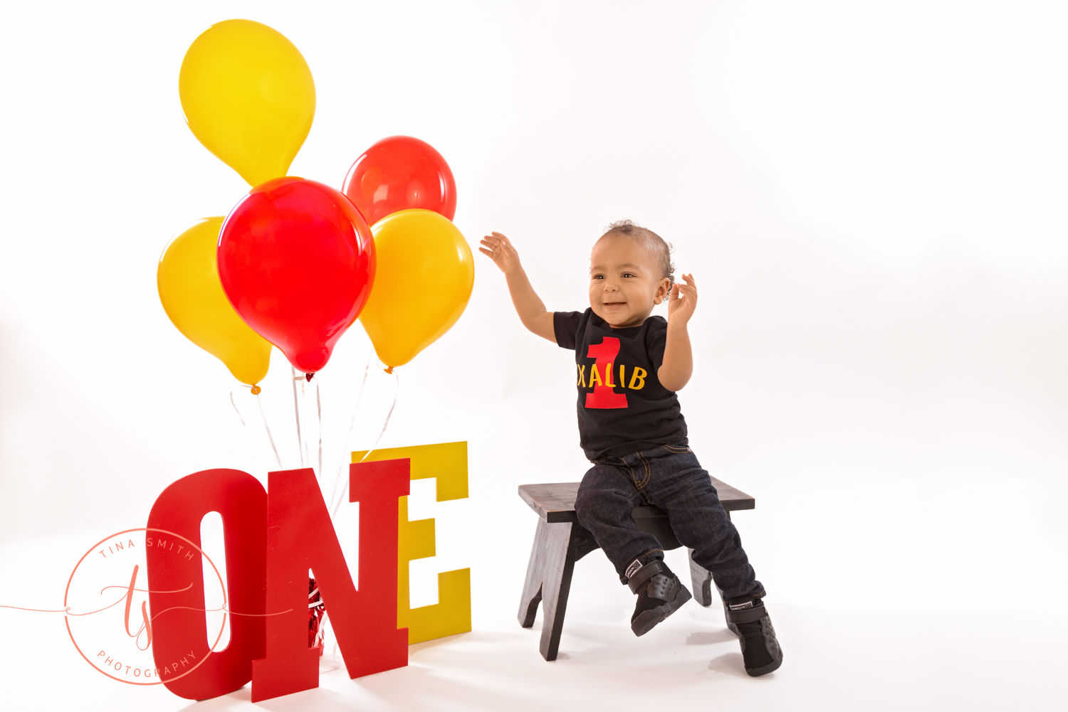 boy in 1 year shirt with mickey mouse and balloons