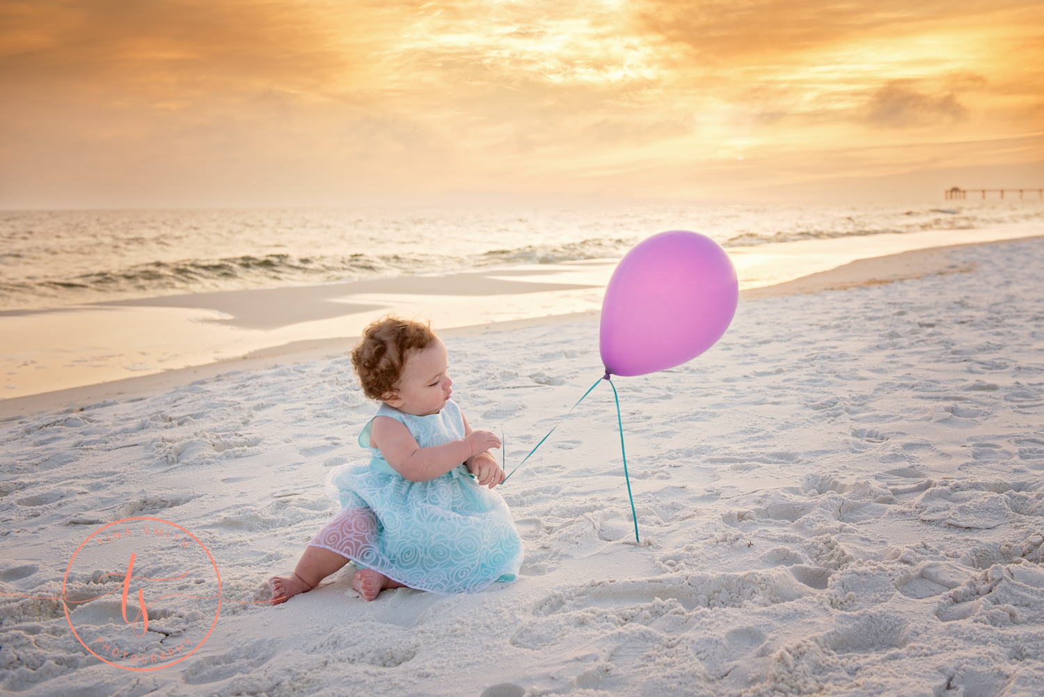 baby with balloon sitting on beach