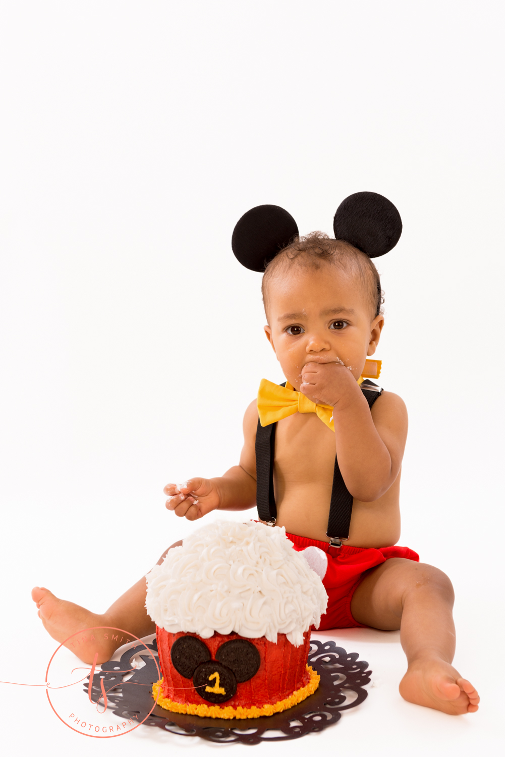 boy wearing mickey mouse ears eating cake for 1 year cake smash