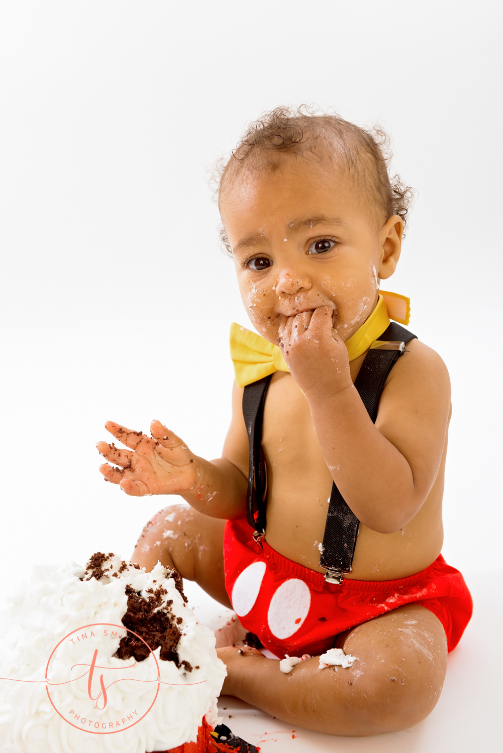 boy in mickey mouse outfit eating cake in destin studio