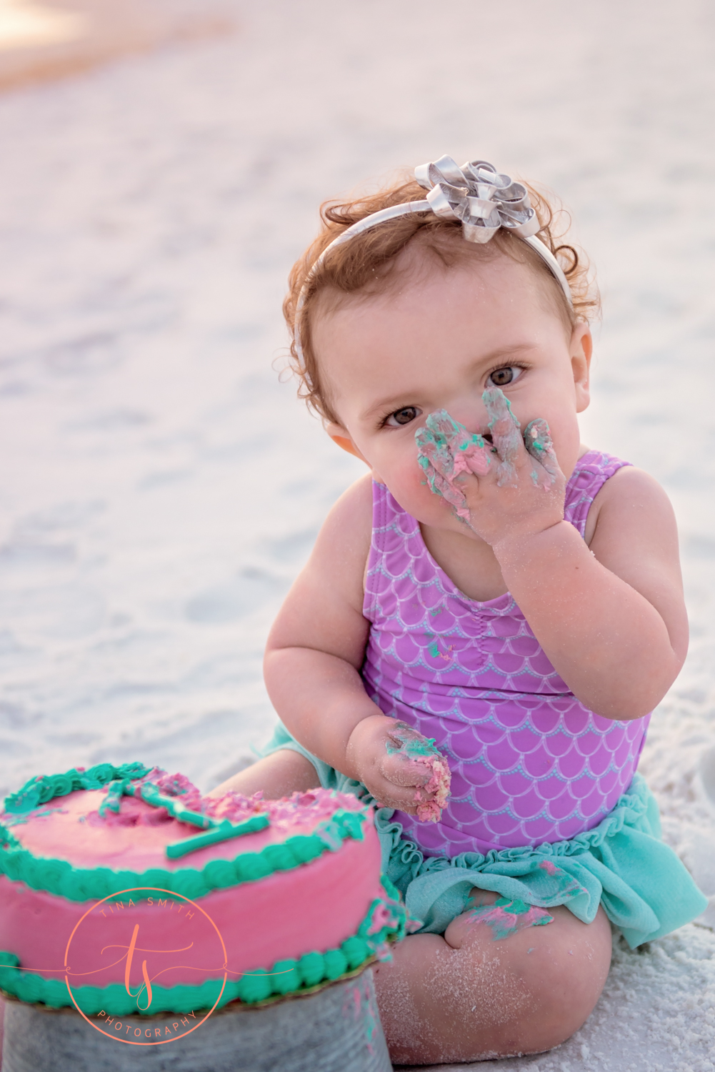 baby smashing cake into her face on beach in destin