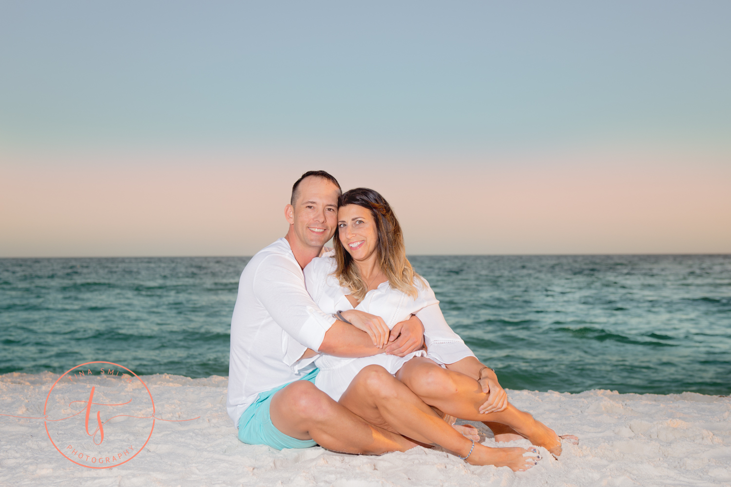 couple sitting on beach smiling for photography