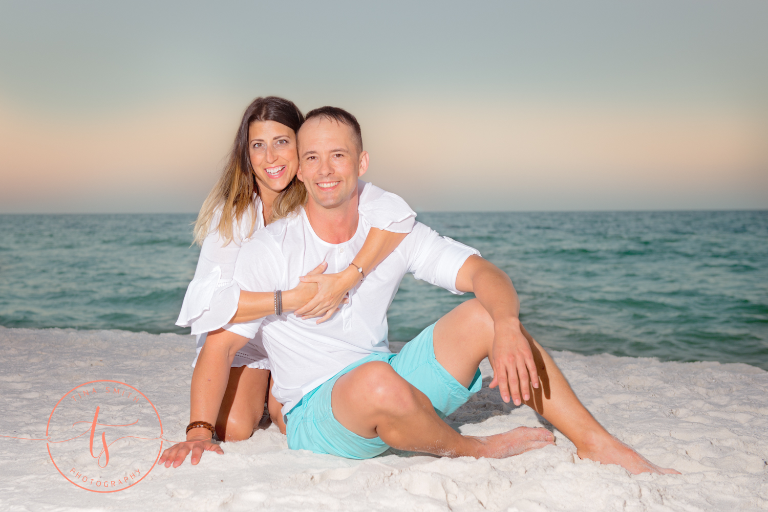 couple hugging on the beach smiling for photographer
