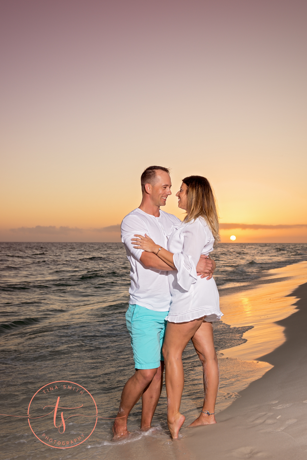 couple standing in water on beach in destin at sunset