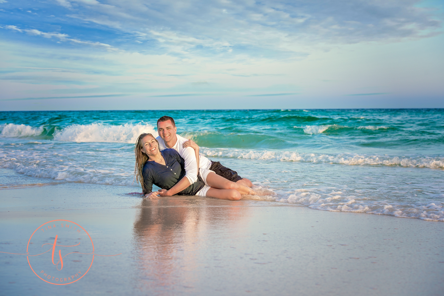 couple in the water on beach in destin posing for engagement photography