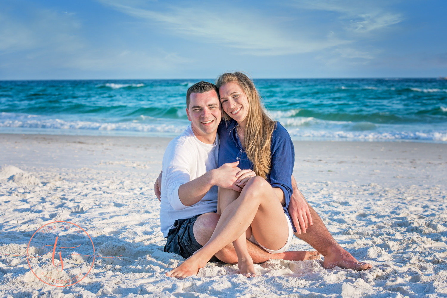 couple sitting on beach huggins showing off engagement ring
