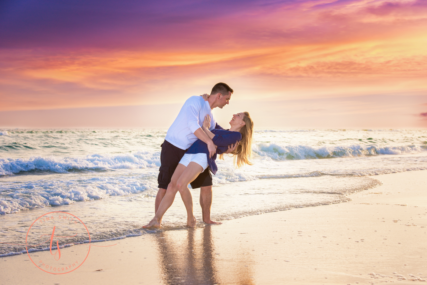 engaged couple dipping at sunset in water on beach in destin