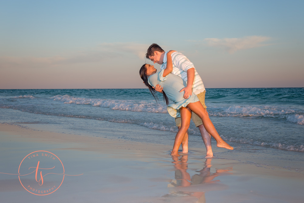 couple on beach in destin posing for photographer