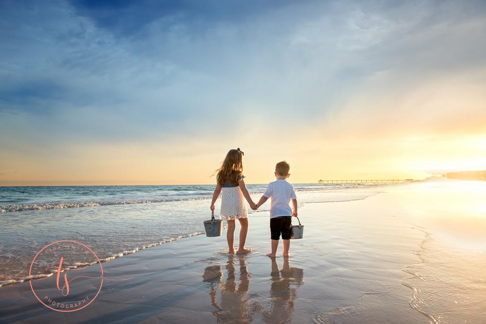 children walking down beach in destin at sunset