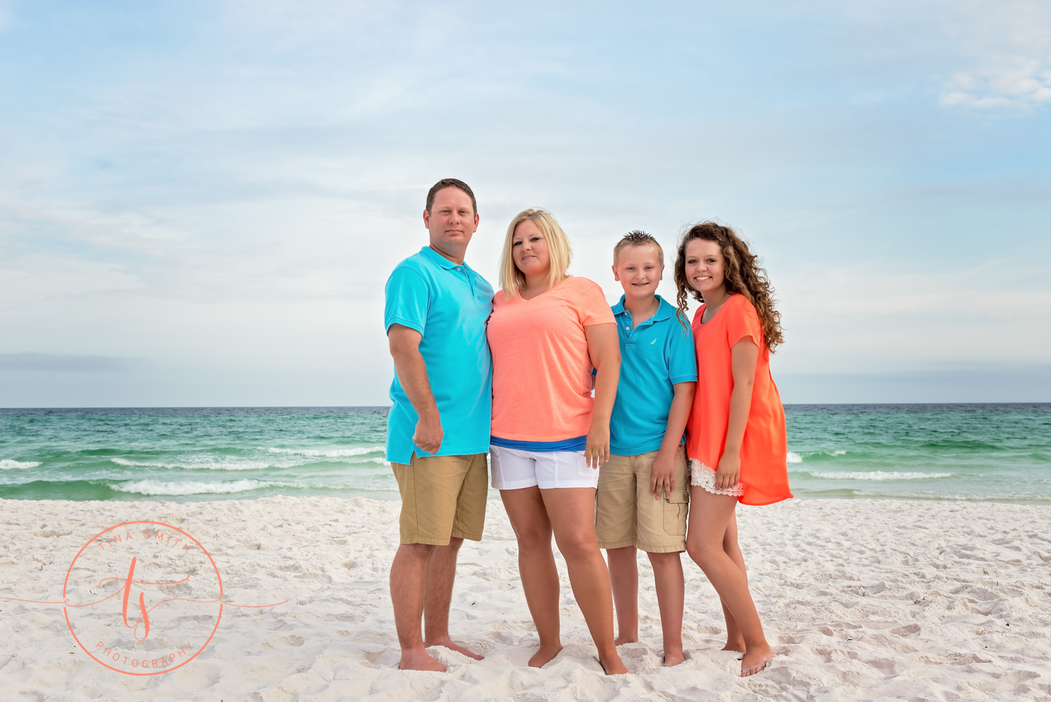 family wearing teal and orange standing on beach for portraits